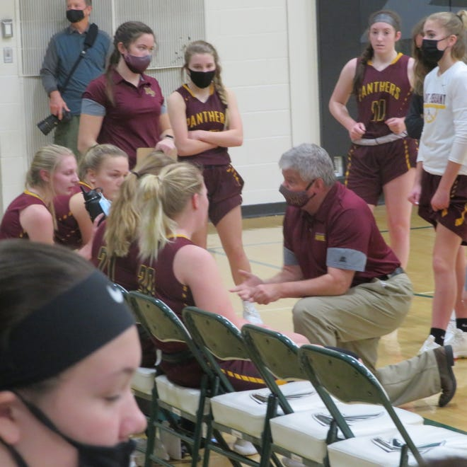 Mount Pleasant High School girls basketball coach Curt Watson discusses strategy with his team during Saturday's game at West Burlington.