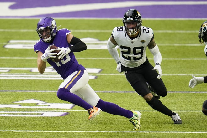 Minnesota Vikings wide receiver Adam Thielen, left, runs from a Jacksonville Jaguars defender during the first half of an NFL football game, Sunday, Dec. 6, 2020, in Minneapolis. (AP Photo/Jim Mone)