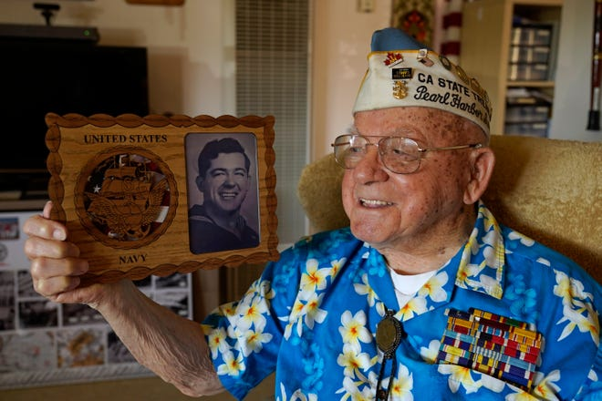 Mickey Ganitch, a survivor of the 1941 attack on Pearl Harbor, holds a plaque with a picture of himself as a young sailor, while sitting in the living room of his home in San Leandro, Calif. Nov. 20, 2020. The 101-year-old has traveled to Hawaii for the anniversary of the attack almost every year of the past 15 to remember those killed. But this year, nearly eight decades after the bombing that launched the U.S. into World War II, the coronavirus pandemic is forcing him to observe the moment from afar in California. (AP Photo/Eric Risberg)