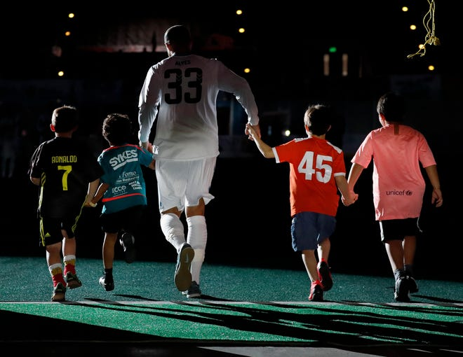 Florida Tropics player Rafa Alves  runs on to the field with some young reinforcements during introductions before a 2019 game at The RP Funding Center in Lakeland. Alves chose to re-sign with the team this past offseason.