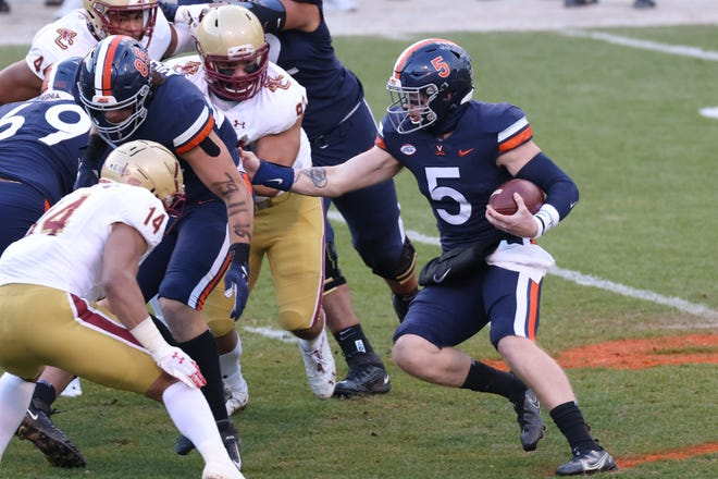 Virginia Cavaliers quarterback Brennan Armstrong (right) runs with the ball as Boston College Eagles linebacker Max Richardson (front left) defends in the first quarter at Scott Stadium.