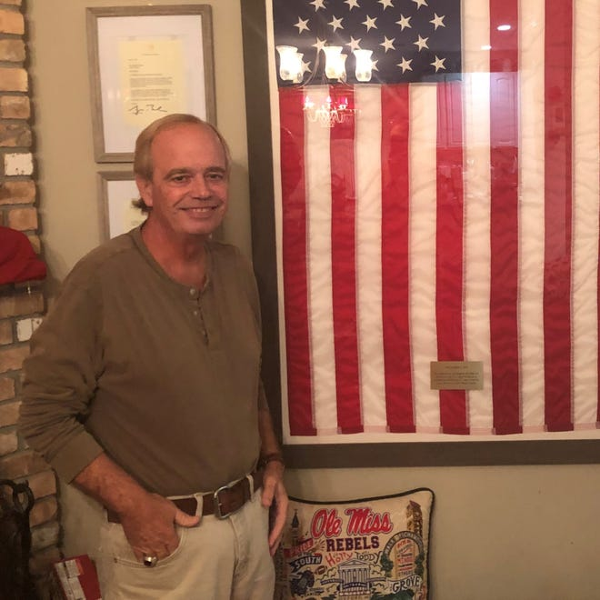 Mike Fleming, who taught AP U.S. History at Forest Hill and Jupiter High Schools for 37 years before retiring in July, stands in front of a flag that was displayed at the U.S. Capitol in his honor Sept. 1. A group of Fleming's former students and parents arranged to have the flag flown to celebrate his dedication to teaching.