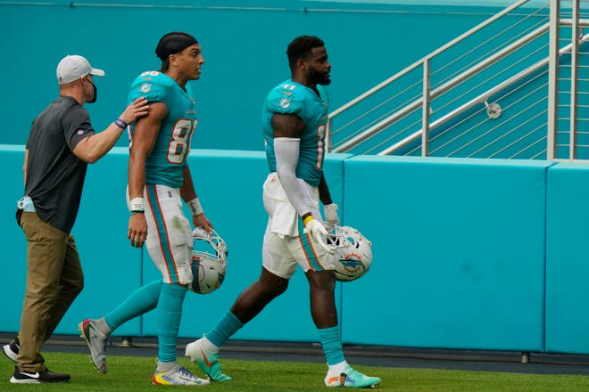 Dolphins receivers Mack Hollins (center) and DeVante Parker are led off the field after being ejected following a fight during the second half Sunday vs. the Cincinnati Bengals.