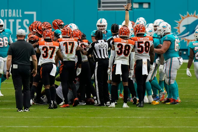 NFL referees attempt to stop a fight on the field during the second half of an NFL football game between the Miami Dolphins and the Cincinnati Bengals, Sunday, Dec. 6, 2020, in Miami Gardens, Fla.
