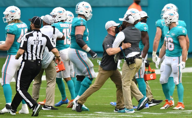 A member of the Dolphins staff holds back Miami Dolphins head coach Brian Flores during an altercation between the Dolphins and the Cincinnati Bengals in the fourth quarter at Hard Rock Stadium in Miami Gardens, December 6, 2020.