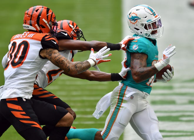Dolphins rookie Lynn Bowden (15) is pushed out of bounds after a big gain Sunday by Cincinnati Bengals free safety Jessie Bates (30) and teammate William Jackson.