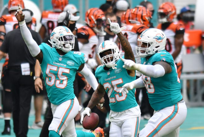Miami Dolphins cornerback Xavien Howard (25) celebrates an interception in the first half with teammates Jerome Baker (55) and Raekwon Davis (98) at Hard Rock Stadium in Miami Gardens, December 6, 2020.