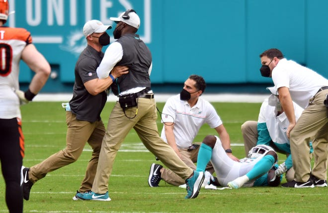Dolphins coach Brian Flores is restrained as Jakeem Grant receives treatment after an illegal hit.
