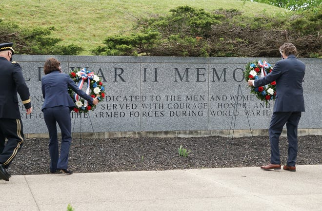 Gov. Gina Raimondo, left, and Lt. Gov. Dan McKee place wreaths during a Memorial Day ceremony at the Rhode Island Veterans Cemetery in Exeter last May.