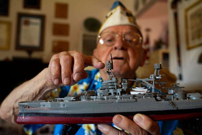 Mickey Ganitch, 101,  holds up a model of the USS Pennsylvania and points to where he served as a lookout during the 1941 attack on Pearl Harbor, in his home in San Leandro, Calif.