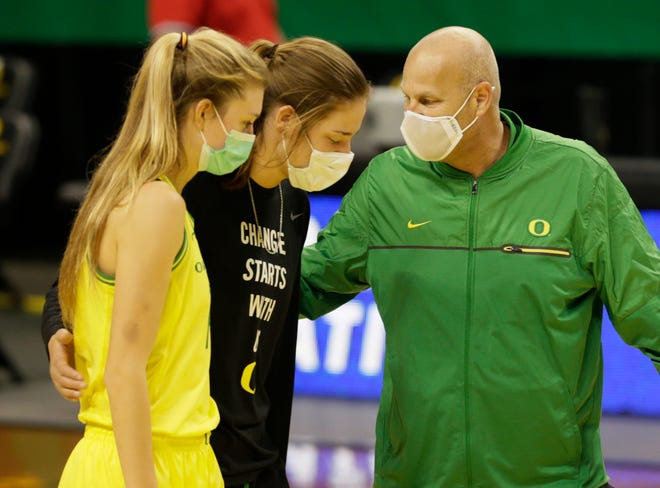 Oregon's Lydia Giomi, left, an injuried Sedona Prince and coach Kelly Graves leave the court after the win over Utah.