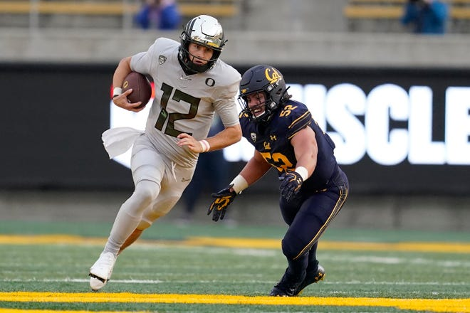 Oregon quarterback Tyler Shough (12) runs past California linebacker Braxten Croteau (52) during the first half of Saturday's game in Berkeley, Calif.
