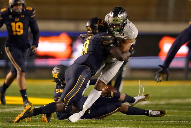 Oregon wide receiver Johnny Johnson III fumbles after being hit by California linebacker Kuony Deng on the Ducks' final possession of the game. California won 21-17.