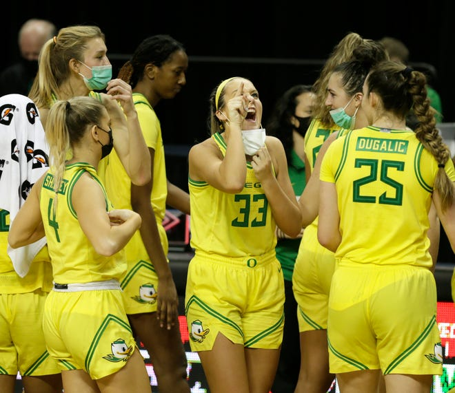 Oregon's Sydney Parrish, center, points to the scoreboard after the Ducks dispatched Utah 85-43.