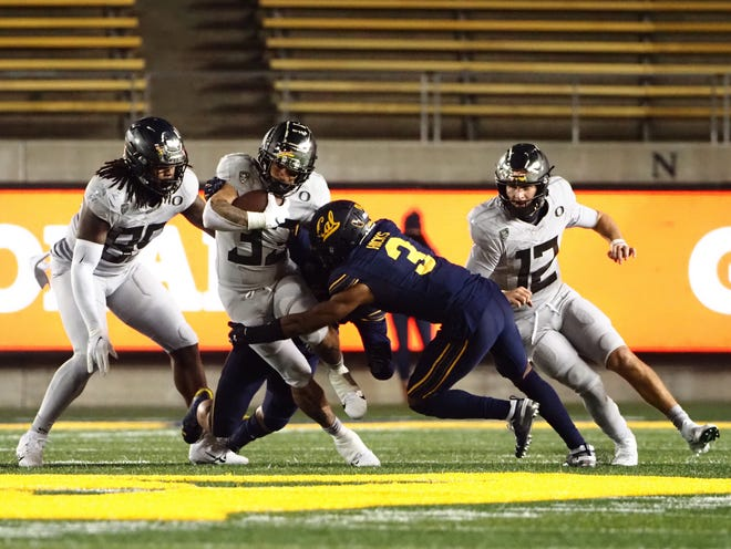 Oregon running back Cyrus Habibi-Likio (33) takes on California safety Elijah Hicks (3) during the third quarter on Saturday.