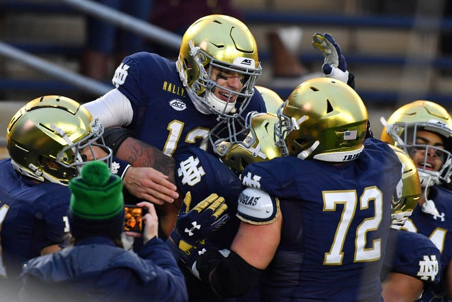 Notre Dame quarterback Ian Book (12) celebrates after running for a touchdown against Syracuse Saturday, Dec. 5, 2020, in South Bend, Ind.