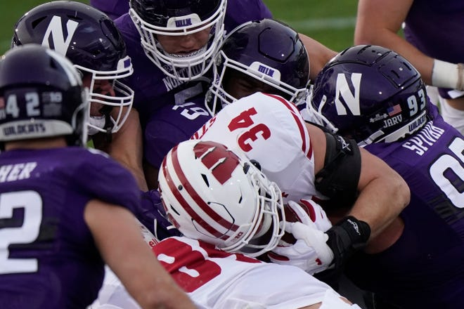 Wisconsin fullback Mason Stokke (34) is tackled by a host of Northwestern defenders during the first half of an NCAA college football game in Evanston, Ill., on Saturday, Nov. 21, 2020. Northwestern won 17-7.