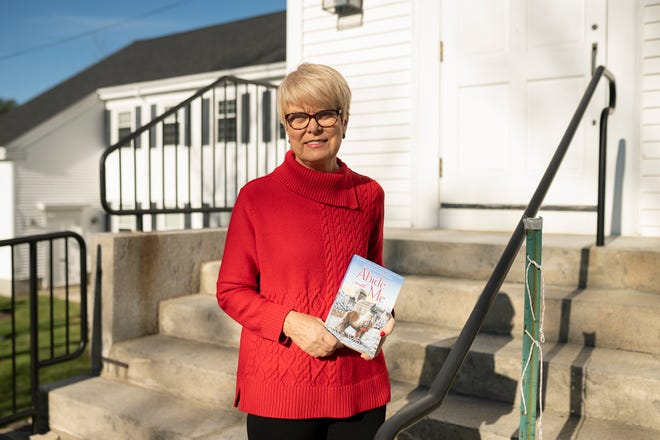 """Rev. Jane Willan, minister of First Congregational Church in Paxton, holds her latest murder mystery, """"Abide With Me.""""'"""