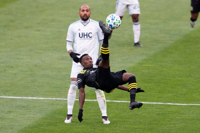 Columbus Crew defender Harrison Afful, foreground, plays for the ball against Revolution forward Teal Bunbury during the first half of the Major League Soccer Eastern Conference final.