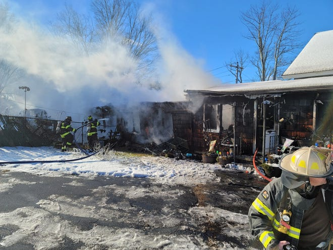 Firefighters tackle a three-alarm blaze at 15 Dennison Lane in Southbridge on Sunday. No injuries were reported.