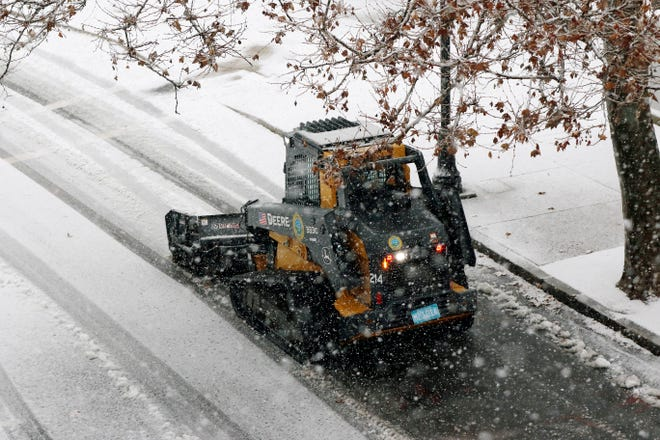 A snow clearing machine cleans a road during heavy snow Saturday in Marlboro. The northeastern United States was hit with its first big snowstorm of the season.