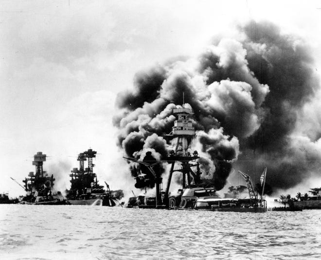 Three U.S. battleships are hit from the air during the Japanese attack on Pearl Harbor on Dec. 7, 1941. Japan's bombing of U.S. military bases at Pearl Harbor brings the U.S. into World War II. From left are: USS West Virginia, severely damaged; USS Tennessee, damaged; and USS Arizona, sunk.