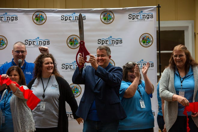 Newberry City Commissioner Tim Marden holds up a pair of scissors after a ceremonial ribbon cutting to mark the opening of the Springs County Welcome Center on Sunday in High Springs. [SAM THOMAS/SPECIAL TO THE SUN]