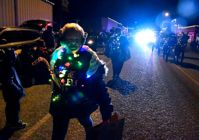 Sharon Wilcoxen, the principal of Cisco Elementary School, wears festive lights as she marches with others from her school's office during the Holly Jolly Christmas Parade in Cisco on Thursday.