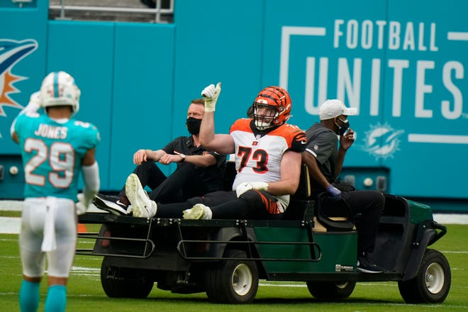 Cincinnati Bengals offensive tackle Jonah Williams (73) is assisted off the field during the second half of an NFL football game against the Miami Dolphins, Sunday, Dec. 6, 2020, in Miami Gardens, Fla. (AP Photo/Wilfredo Lee)