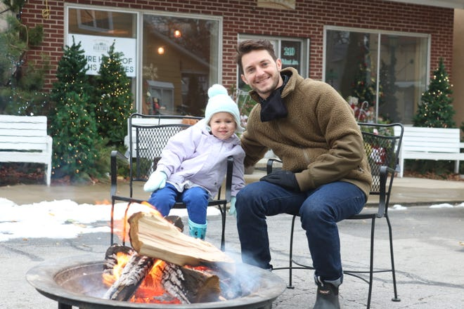 Jacob Abernathy, and his daughter, Virginia, 3, of Los Angeles, California, warm up at a fire pit in downtown Lakeside on Saturday.