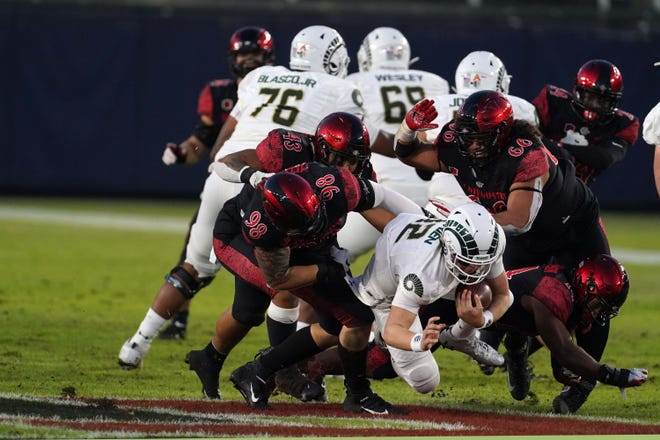 Colorado State Rams quarterback Patrick O'Brien (12) is sacked by San Diego State Aztecs defensive lineman Connor Mitchell (98)) and defensive lineman Jonah Tavai (66) in the first half at Dignity Health Sports Park on Dec. 5, 2020.