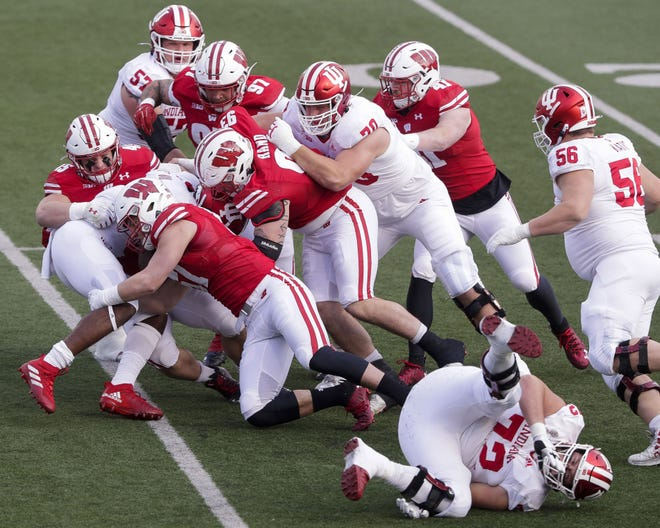 Wisconsin's Leo Chenal (45) and Jack Sanborn (57) tackle Indiana's Stevie Scott III on Dec. 5, 2020, at Camp Randall Stadium.