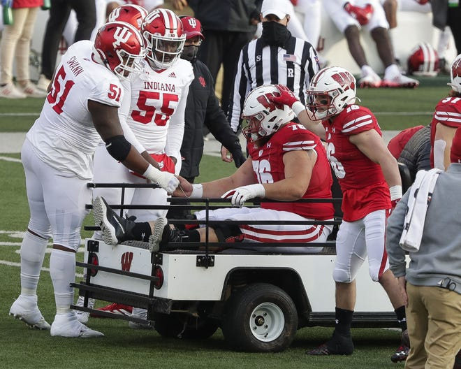 Kayden Lyles  receives well wishes from Indiana's Jovan Swann (51) and C.J. Person  and Wisconsin's Jack Dunn (16) before being carted off the field with an injury Saturday.