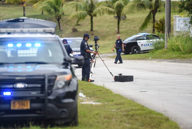 Guam Police Department Highway Patrol Division officers conduct an investigation at the scene of a fatal traffic crash in Sumay on Dec. 6, 2020.