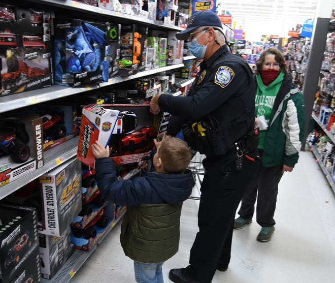 Lakeview police officer Steve Raines helps 6-year-old Joshua Snurr pull a set of remote-controlled cars off the shelf Saturday morning at the Mountain Home Walmart during the Fraternal Order of Police Lodge 45's annual Shop With a Cop event. FOP members took 110 kids on shopping sprees Saturday as part of the event.