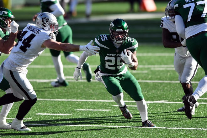 New York Jets running back Ty Johnson finds a hole against the Las Vegas Raiders in the first half Sunday. Johnson had a big day, rushing for 104 yards and scoring a touchdown.