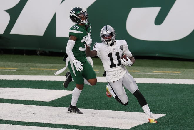 Henry Ruggs III of the Las Vegas Raiders reacts after scoring a touchdown in the final seconds of the second half as Josh Adams #36 of the New York Jets looks on at MetLife Stadium on December 06, 2020 in East Rutherford, New Jersey.