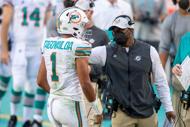 Miami Dolphins head coach Brian Flores talks to Miami Dolphins quarterback Tua Tagovailoa (1) on the sidelines as the Dolphins take on the Los Angeles Chargers during an NFL football game, Sunday, Nov. 15, 2020, in Miami Gardens, Fla.