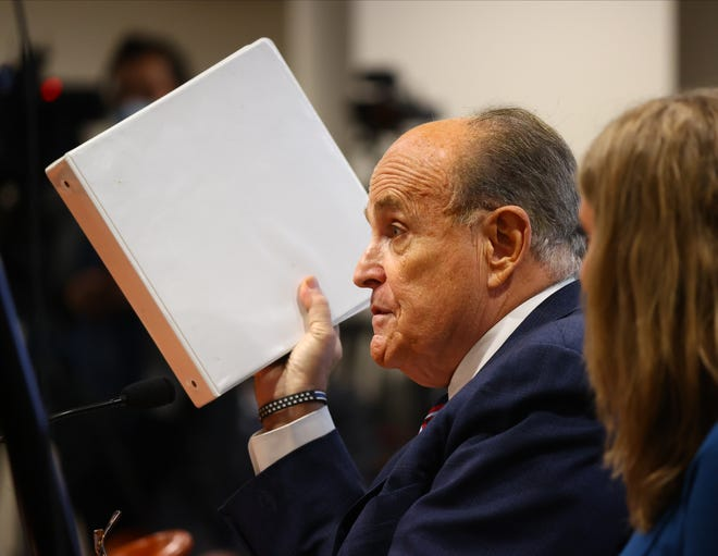 President Donald Trump's personal attorney Rudy Giuliani speaks as Jenna Ellis, a member of the president's legal team looks on at an appearance before the Michigan House Oversight Committee on Dec. 2, 2020 in Lansing, Mich.