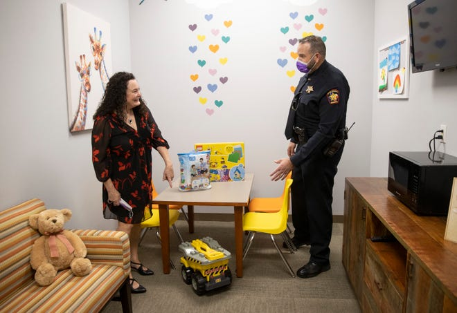 Denise Fonseca, Founder of Room2Hope, and Hays County sheriff's deputy Mark Andrews look at the toys donated by the sheriff's office to a Room2Hope waiting room at the Hays County Government Center in San Marcos on Monday. Room2Hope unveiled the refurbished waiting rooms designed to comfort those facing violent offenders during criminal trials.