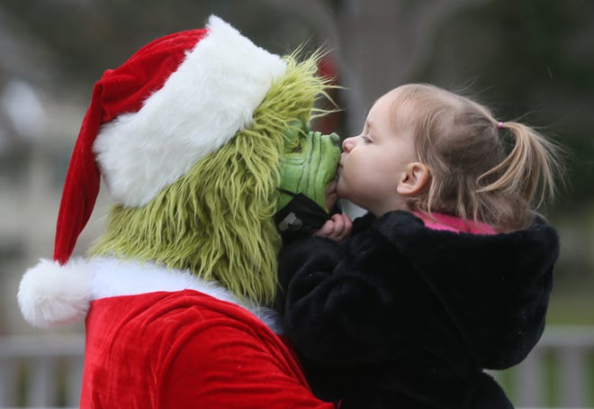 Joel Testa as the Grinch gets a kiss from his daughter Sofia, 2 at Silver Lake Garden Club's traditional Christmas tree lighting on Dec. 6 at Christmas Tree Island along Silver Lake Boulevard. Gift bags for adults and children were handed out to each car as well as an ornament at the annual event. [Mike Cardew/Beacon Journal]