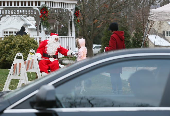Santa greets a young walk-up visitor during Silver Lake Garden Club's traditional Christmas tree lighting on Dec. 6 at Christmas Tree Island along Silver Lake Boulevard. Gift bags for adults and children were handed out to each car as well as an ornament at the annual event that had a different format due to COVID-19 [Mike Cardew/Beacon Journal].