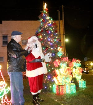 Sebring Mayor James Harp, left, applauds Saturday night as the village's Christmas tree lights up at the corner of Ohio Avenue and 15th Street following Santa's countdown during a celebration.