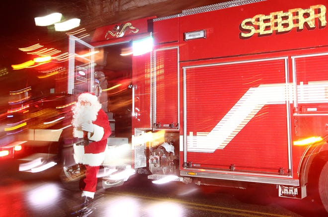 Santa climbs down from a Sebring Fire Department vehicle to greet a crowd Saturday night before a lighting ceremony at Harvest Park.