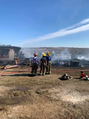 Local volunteer firefighters work to completely extinguish a large structure fire at a residence located off of Miner Road in Love County on Sunday. Two men escaped from the home, but their pet dog did not make it out.
