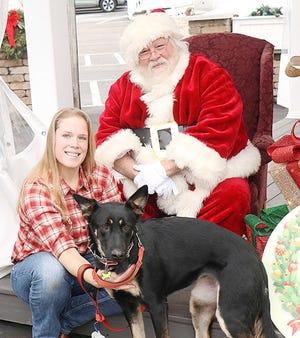 Brittney Filka, Santa Claus, her dog Brynx pose for a photo Sunday during Santa's visit to Grandpa's Cheesebarn in Ashland.