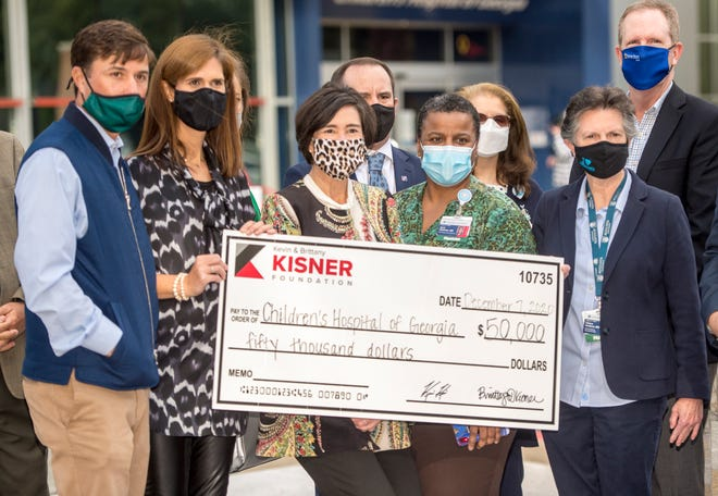 Golfer Kevin Kisner, front row from left, and his wife Kisner Foundation Chairman Brittany Kisner hand over the big check to CEO of Augusta University Health System Katrina Keefer, Dr. April Hartman and Dr. Valera Hudson at the Children's Hospital of Georgia Monday morning December 7, 2020.