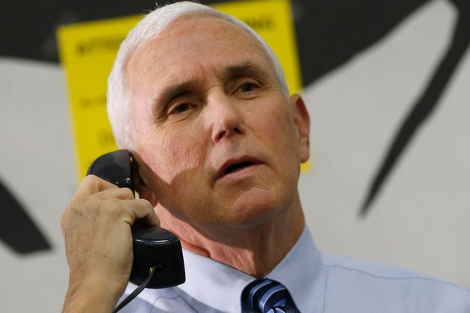 Vice President Mike Pence, left, talks to the staff on an intercom during an April tour of a Walmart Distribution Center in Gordonsville, Va. He will appear in Augusta Thursday to campaign for sens. Kelly Loeffler and David Perdue. (AP Photo/Steve Helber)
