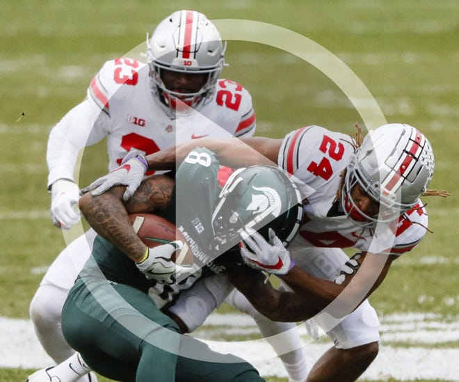 In this file photo, Ohio State Buckeyes cornerback Shaun Wade (24) brings down Michigan State Spartans wide receiver Jalen Nailor (8) during the third quarter of a NCAA Division I football game between the Michigan State Spartans and the Ohio State Buckeyes on Saturday, Dec. 5, 2020 at Spartan Stadium in East Lansing, Michigan.