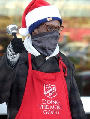 Conrad Brown, wearing a face-covering, rings a bell for the Columbia Salvation Army in front of the Conley Avenue Hy-Vee grocery store on Monday. Masks have been required in Columbia since early in the summer.